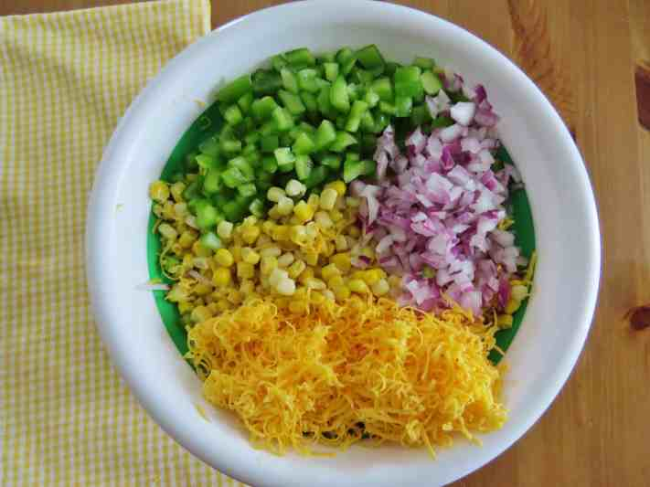 frozen corn, diced green peppers, diced red onion, shredded cheese in a bowl