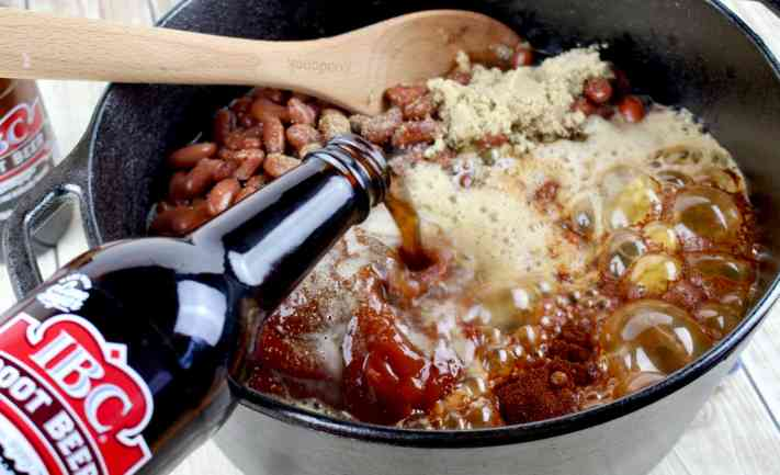root beer being added to pot of beans