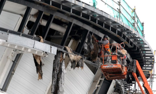 Workmen removing burnt insulation after the fire.