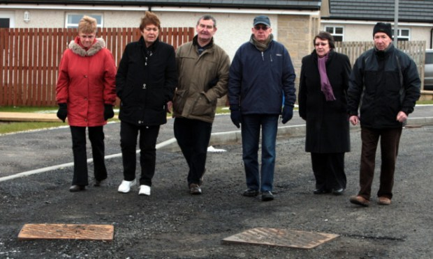 Boswell Knowe residents Wilma Florence, Avril Scott, Ian Florence, Ron and Mary McQueen, and Ian Brown beside some of the raised ironwork on the road that has never been properly surfaced.