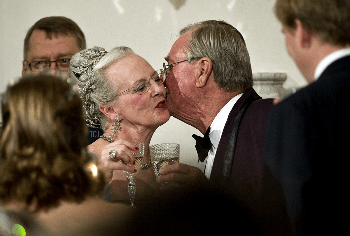 Denmark's Prince Consort Henrik (R) kisses Danish Queen Margrethe during the gala dinner on April 16, 2010, held at the Royal Fredensborg Palace near Copenhagen to celebrate the 70th birthday of the Queen