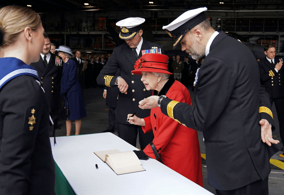 Queen Elizabeth II reacts as she meets military personnel during her visit to the aircraft carrier HMS Queen Elizabeth in Portsmouth, southern England on May 22, 2021