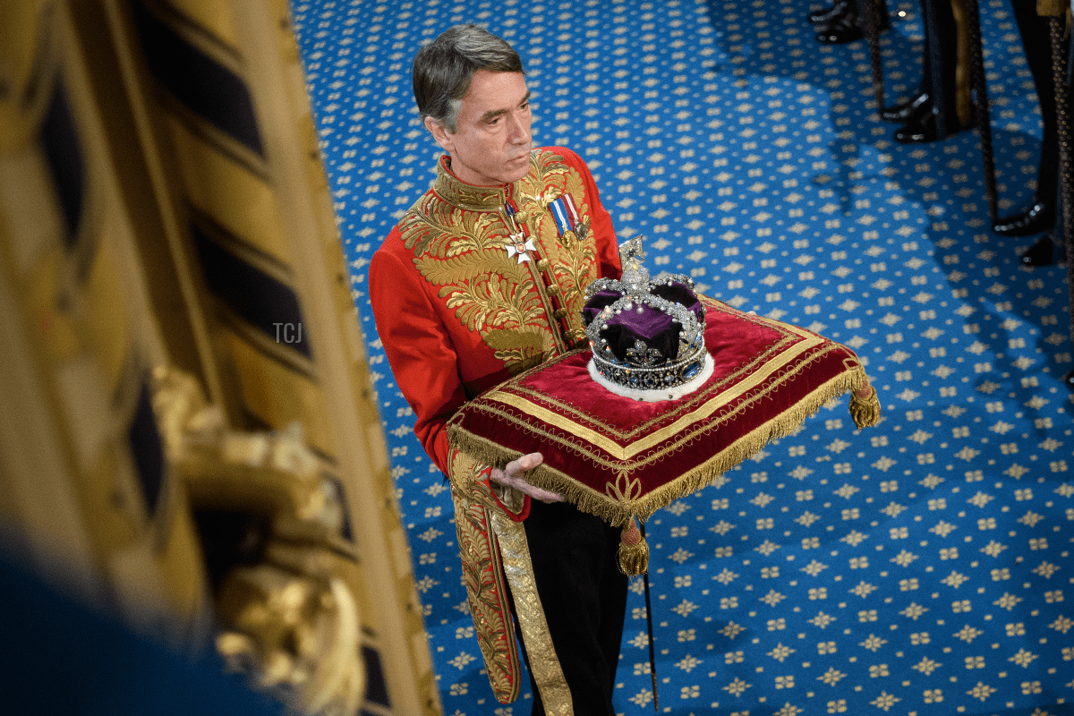The Marquesses of Cholmondeley, in ceremonial uniform, holds the Queen's crown outside the House of Lords after the Queen's speech during the State Opening of Parliament at the Palace of Westminster on October 14, 2019 in London