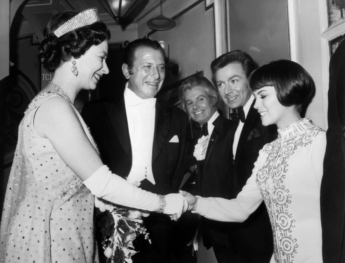 Britain's Queen Elizabeth II (L) shakes hands with French singer Mireille Mathieu in 1969 in London after the French artist performance