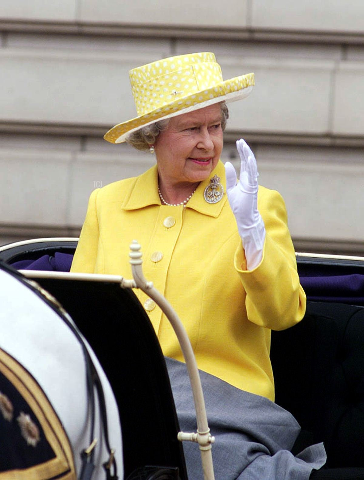 Queen Elizabeth II waves to crowds as she rides in an open carriage on the way to the Trooping the Colour ceremony in London, 12 June 1999