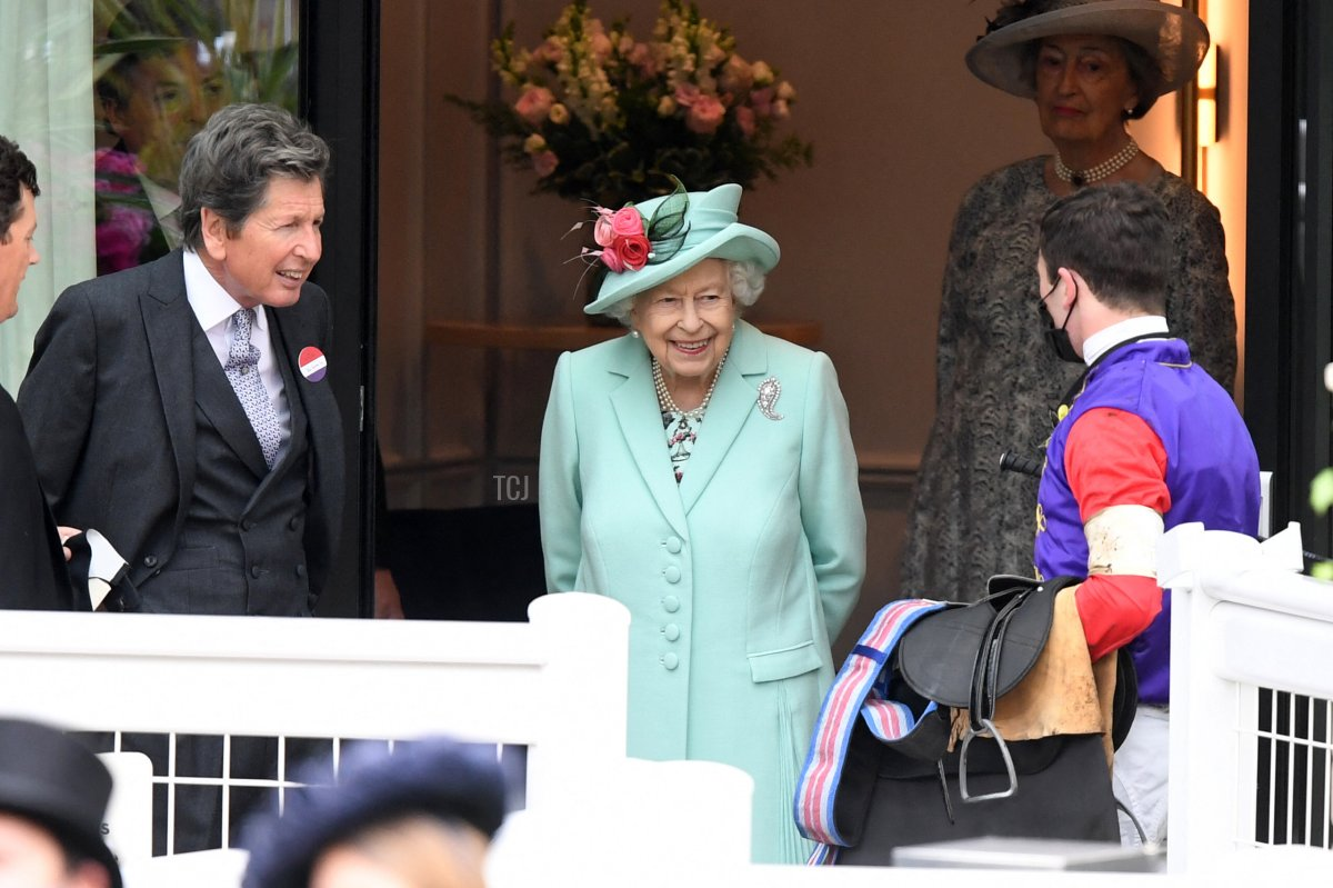 Britain's Queen Elizabeth II smiles as she meets a jockey on the fifth day of the Royal Ascot horse racing meet, in Ascot, west of London on June 19, 2021
