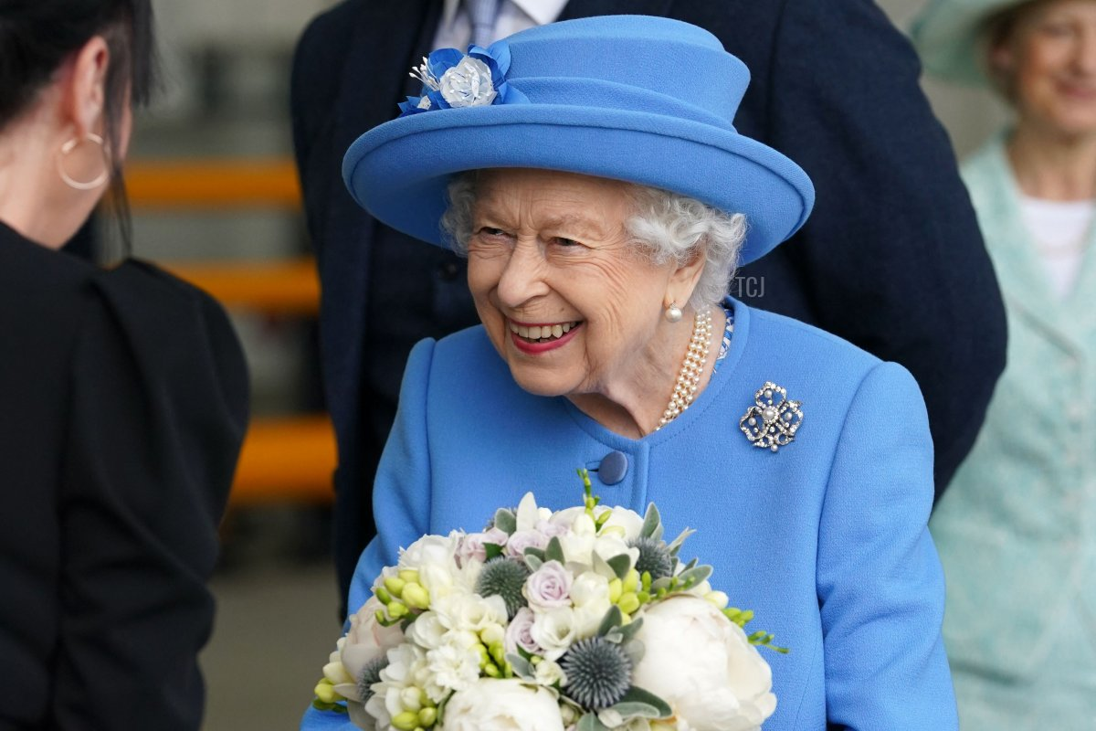 Britain's Queen Elizabeth II receives flowers as she meets employees during a visit to AG Barr's factory in Cumbernauld, east of Glasgow, where the Irn-Bru drink is manufactured on June 28, 2021