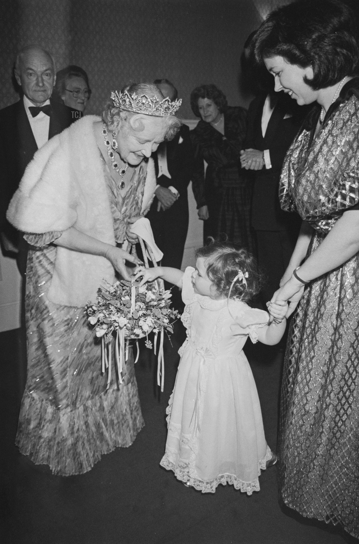 Queen Elizabeth The Queen Mother is greeted by a young girl who presents the royal with a basket of flowers at the royal film premiere of 'A Passage To India', at the Odeon Leicester Square in London, England, 1st March 1985