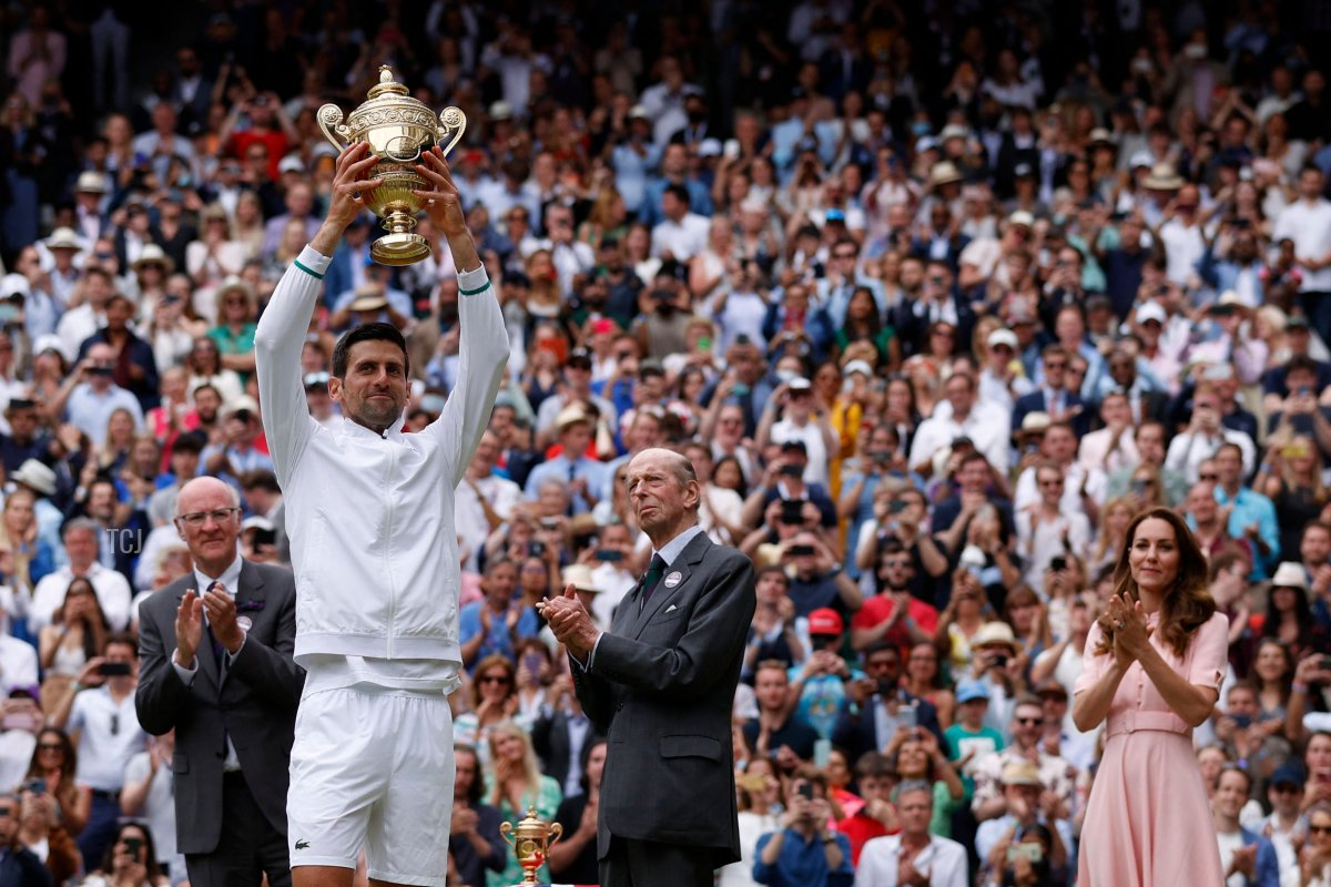 Serbia's Novak Djokovic, with Britain's Catherine (R), Duchess of Cambridge, holds the winner's trophy after beating Italy's Matteo Berrettini during their men's singles final match on the thirteenth day of the 2021 Wimbledon Championships at The All England Tennis Club in Wimbledon, southwest London, on July 11, 2021