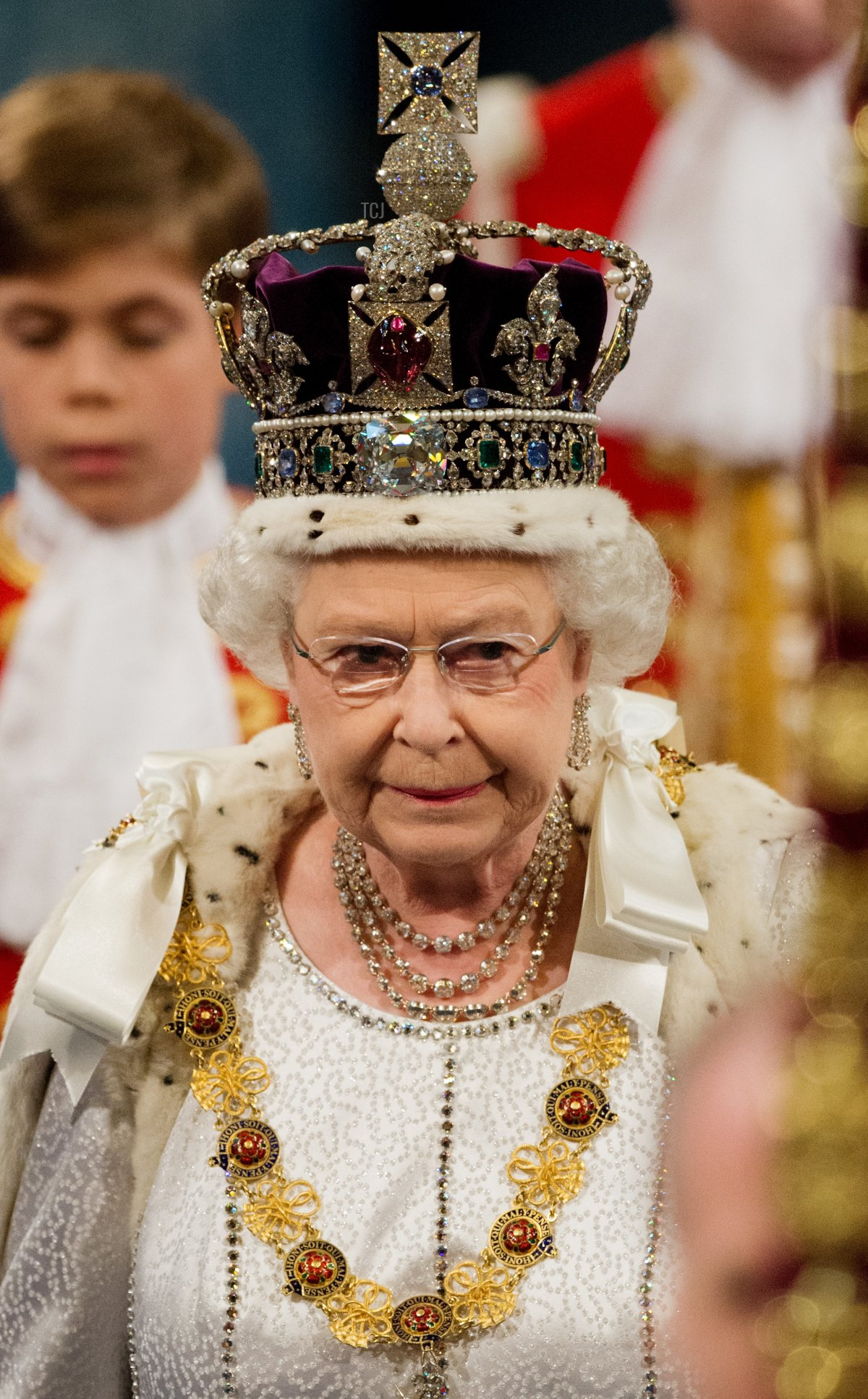 Britain's Queen Elizabeth II wearing the Imperial State Crown walks through the Royal Gallery toward the Chamber of the House of Lords in the Palace of Westminster during the State Opening of Parliament in London on May 9, 2012