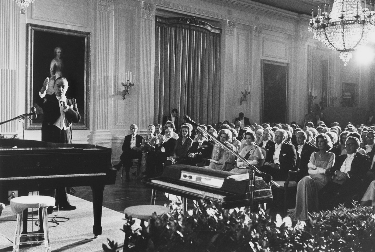 This photograph depicts President Gerald Ford and guests in the center and right of image. A piano sits in the left foreground. Comedian Bob Hope is standing behind and left of piano, gesturing and speaking into microphone, during his monologue for the entertainment portion of the State Dinner held in honor of the Queen of England