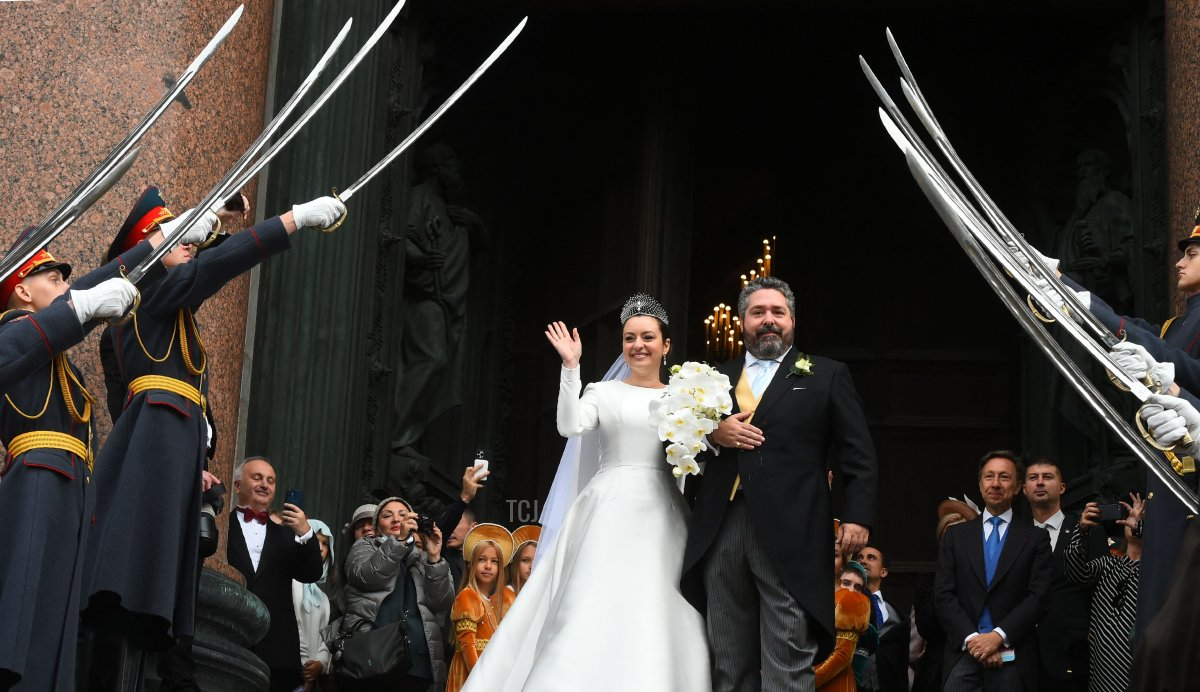 Grand Duke George Mikhailovich Romanov and Victoria Romanovna Bettarini leave the Saint Isaac's Cathedral as Russian honour guards salute them during their wedding ceremony in Saint Petersburg, on October 1, 2021