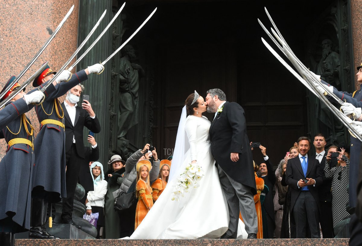 Grand Duke George Mikhailovich Romanov kisses Victoria Romanovna Bettarini as they leave the Saint Isaac's Cathedral as Russian honour guards salute them during their wedding ceremony in Saint Petersburg, on October 1, 2021