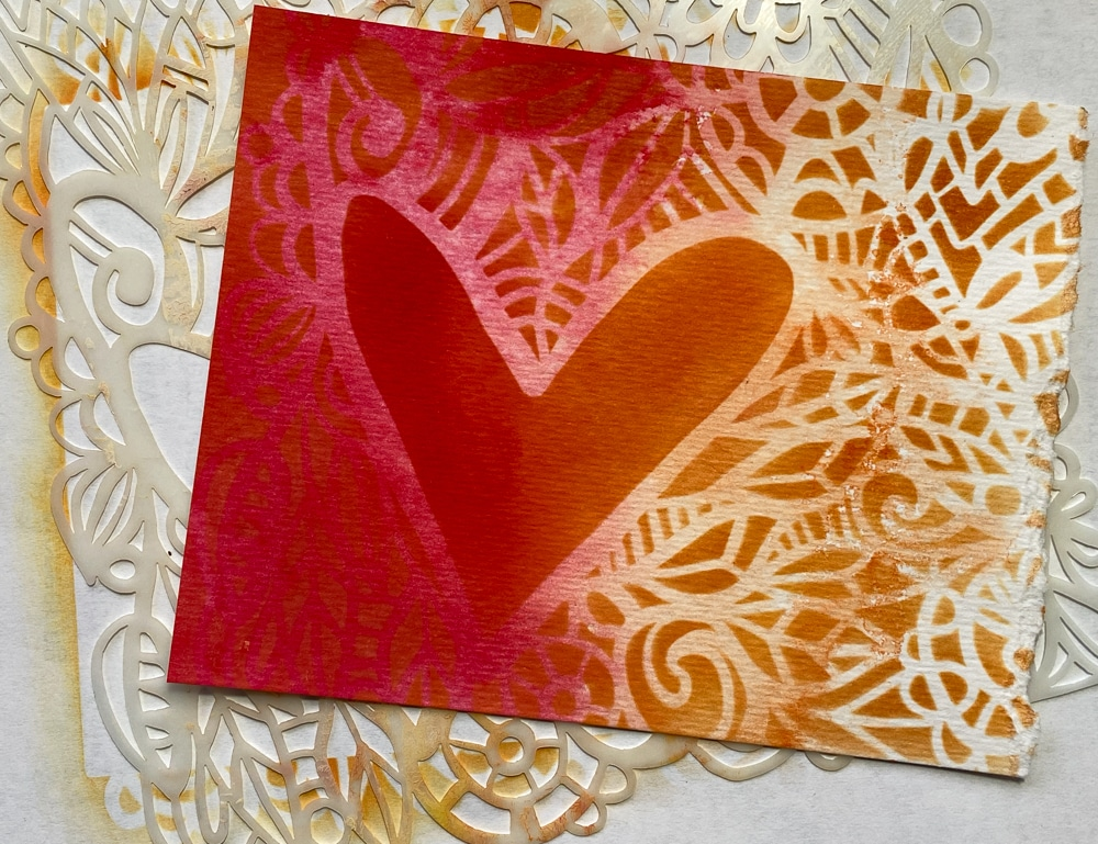 Stenciling over background with Distress Inks and TCW825 Love Frame