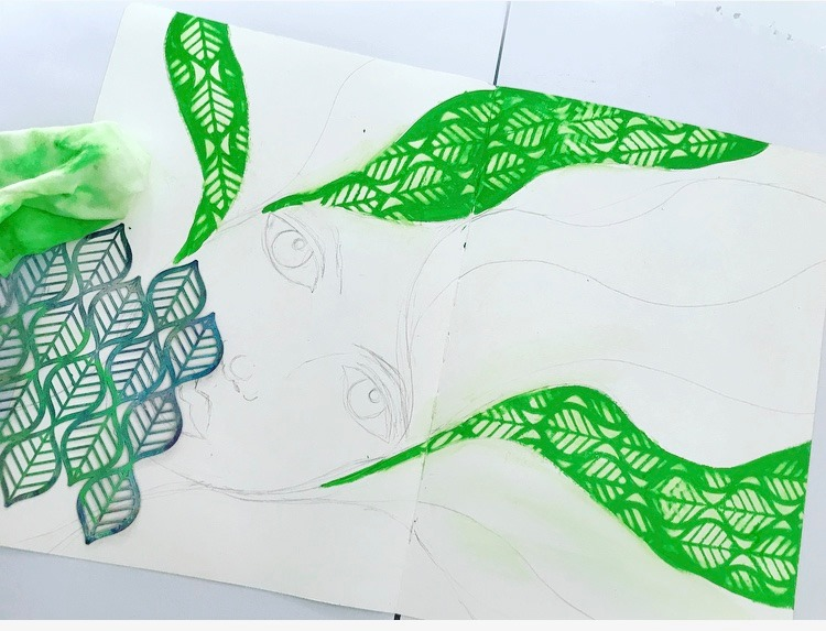 An art journal image with a sketched face with flowing hair. Here some of the strands are painted green and then texture has been created using stencil called 'Deco Leaves'.
