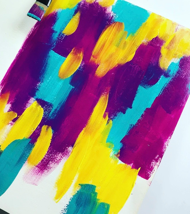 Pink, yellow and blue paint randomly painted onto an art journal page.