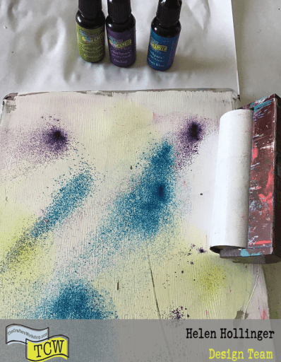 Using a gell press plate, apply white acylic paint over and sprinkle with ColorSparkx. Smoosh around with brayer.