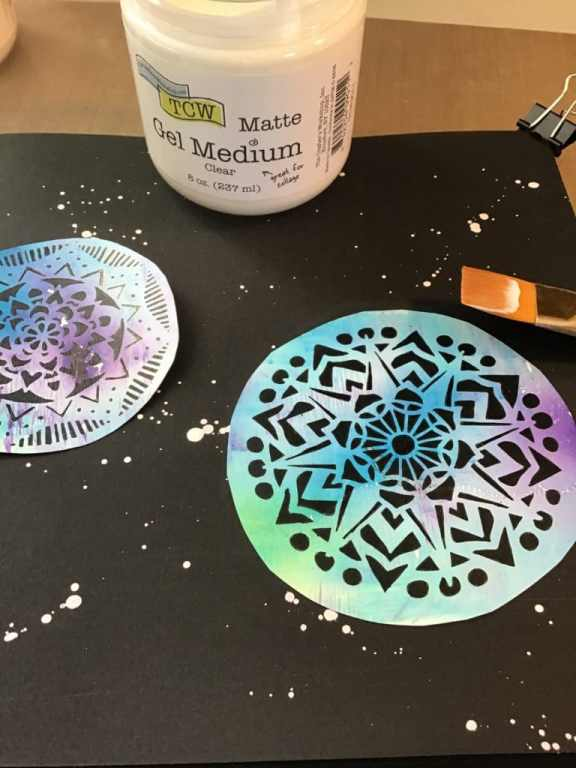 Cut out circles and adhere to a clear gessod black art journal page using Gel Medium