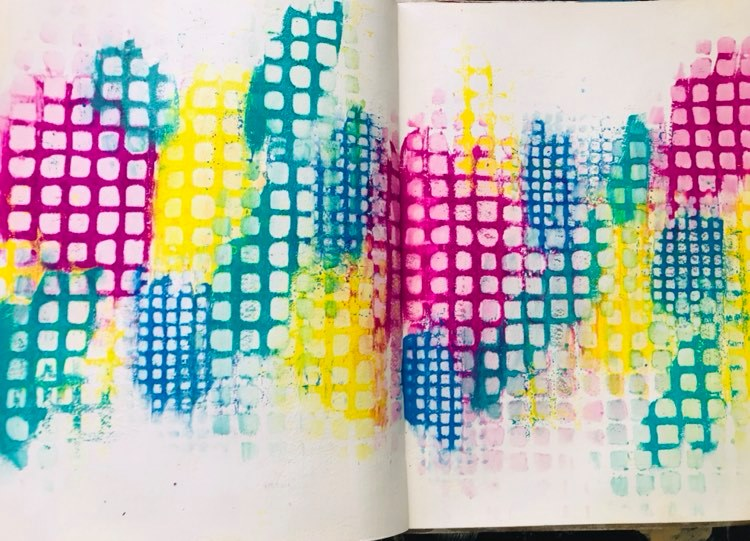 pink, yellow, blue and teal paint in blobs across the page with Stencil work