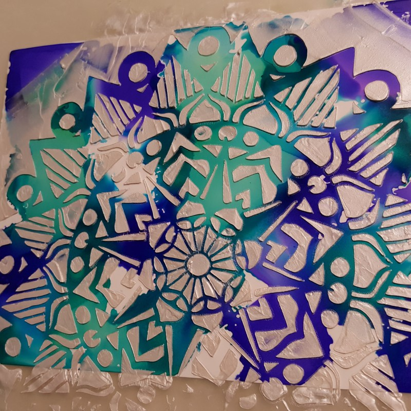 Yupo paper with blue, turquoise, and purple alcohol inks that has been stencilied over using shimmery goodness applied with a palette knife through the striped mandala stencil.