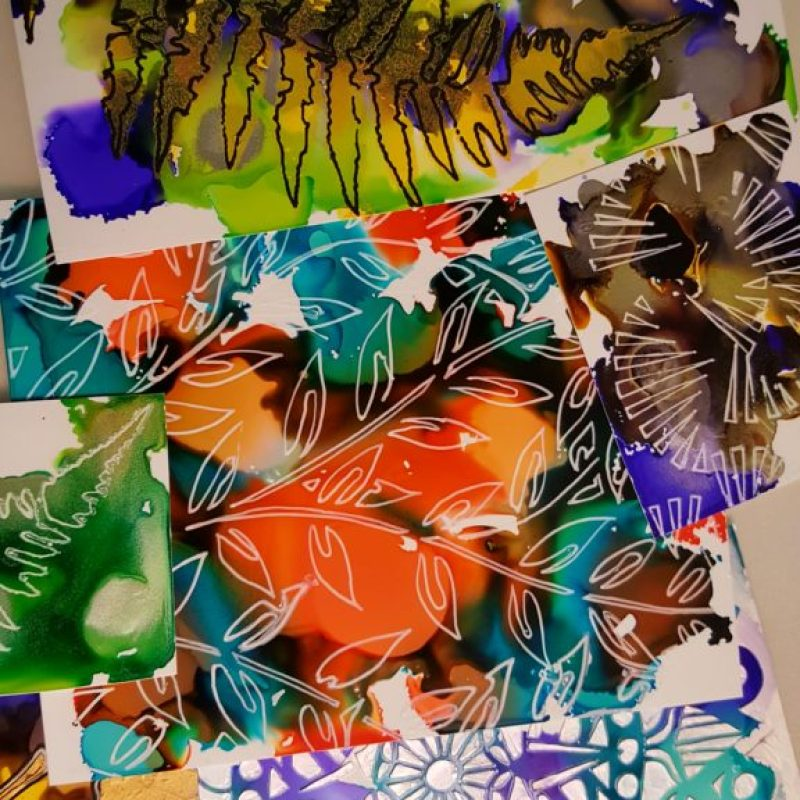 Photo showing multiple works featuring alcohol inks with a variety of stencils and mediums.