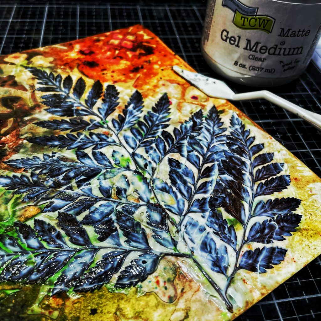 TCW9011 Matte Gel Medium on pressed leaves with a palette knife.