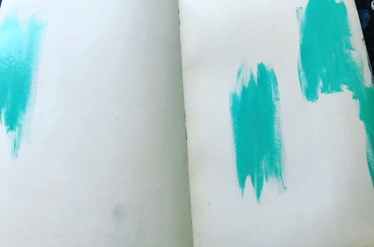 turquoise paint in 3 spots on an art journal background