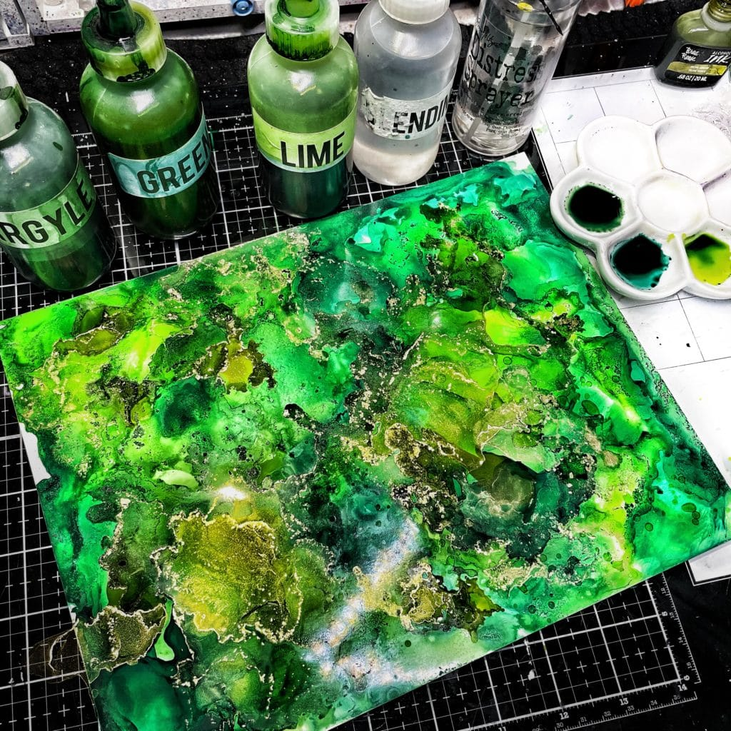 Dried first layer of green and gold alcohol ink on photo paper.