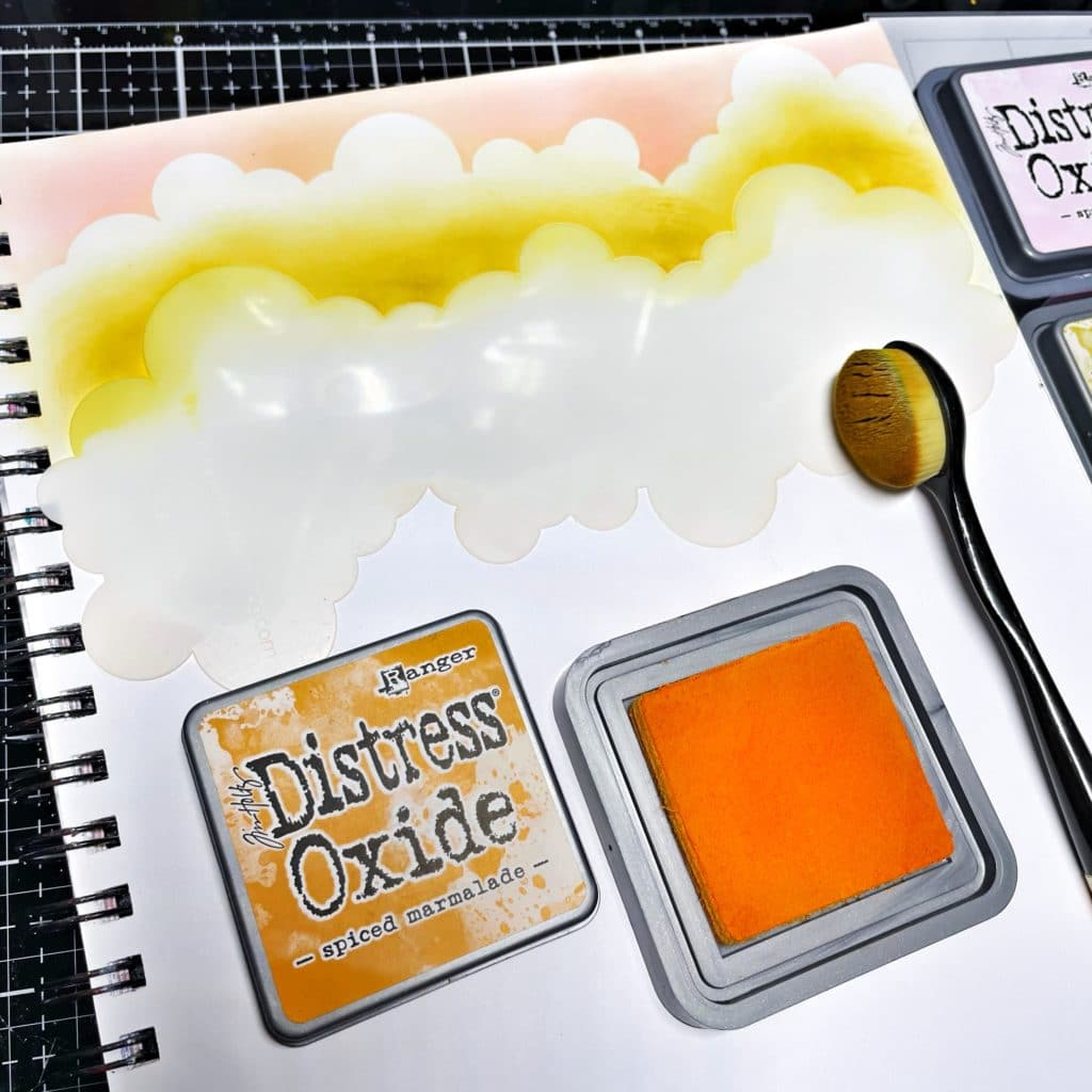 rotated TCW2308 Clouds Slimline Stencil with blended Spiced Marmalade Distress Oxide Ink underneath first layer of clouds