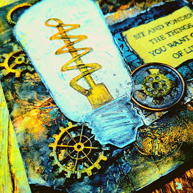 Close up image of the finished artwork taken from the bottom left corner, showing the bottom of the light bulb, multiple wooden and metal gears, and a bit of the sentiment to the right of the light bulb.
