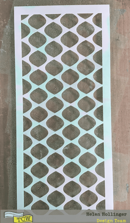 I first smooshed some green ink over my gelli plate. I placed TCW2317 Fence Grid Slimline Stencil over this and took a print off to remove the green ink from the middle parts of the stencil.