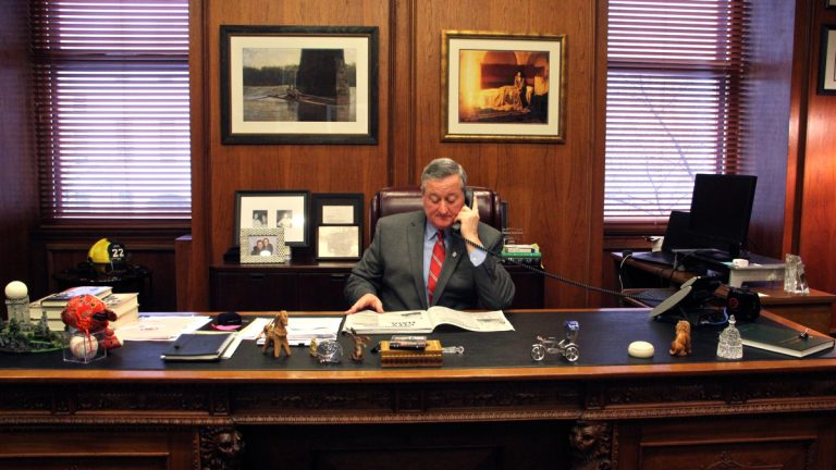 The image of a mayor behind the desk.