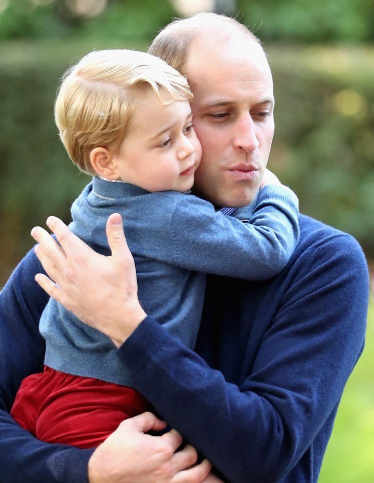 Prince George hugs his father, Prince William, at the children's party. Splash news