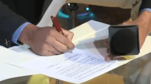 exciting photo of man signing paperwork