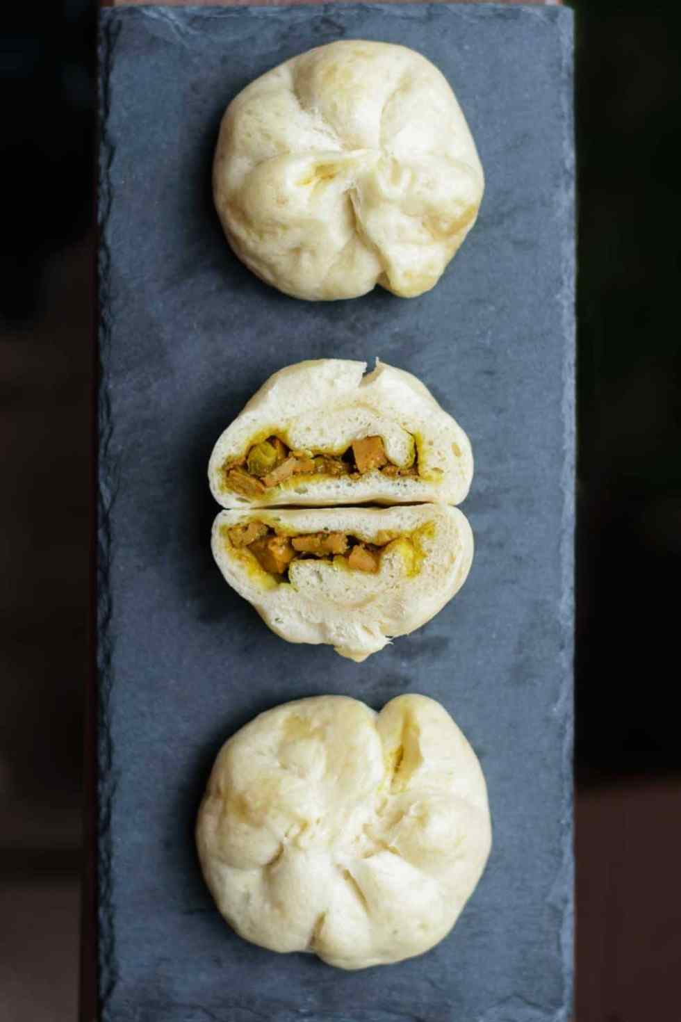 3 curry seitan siopao on a black slate with the middle one cut open. Dark background.
