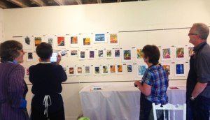 students looking at finished prints on the magnetic exhibition wall
