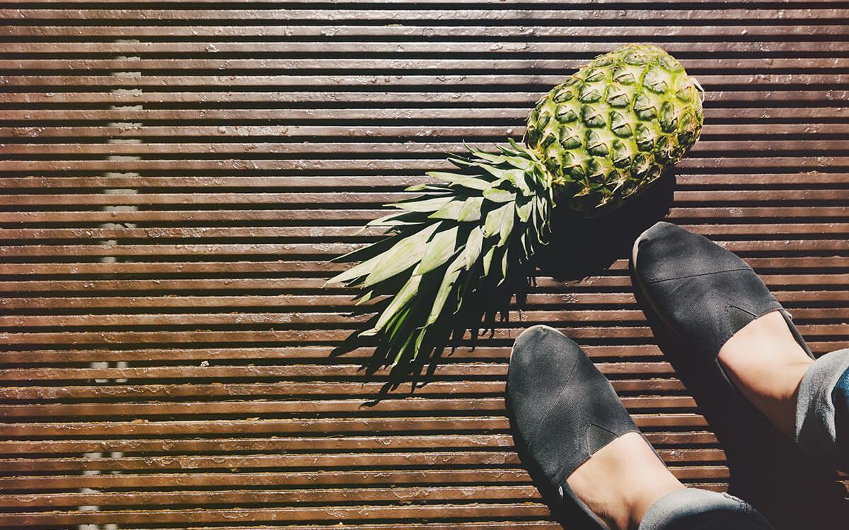 voeten van een vrouw met ananas op de grond