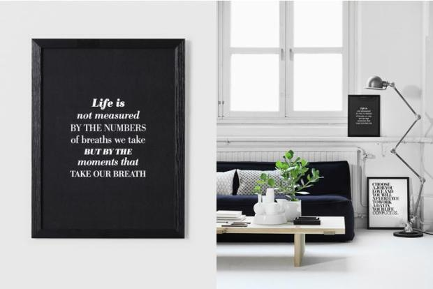Typography Interior Design White Living Room with Black Couch and Framed Quotes Floor Lamp Indoor Plants Large Windows Wood Coffee Table