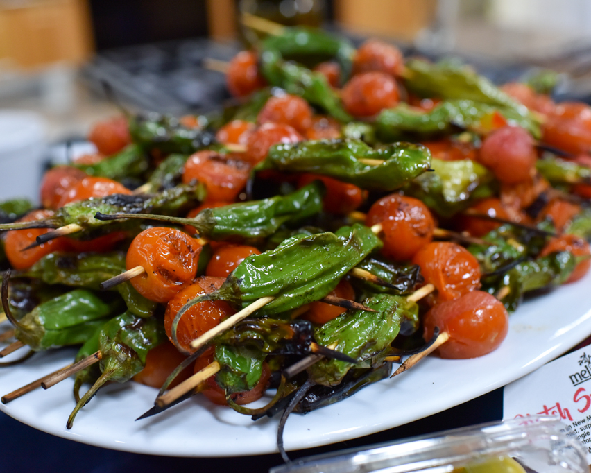 Skewered Shishito Peppers with Cherry Tomatoes and Chimichurri Sauce.