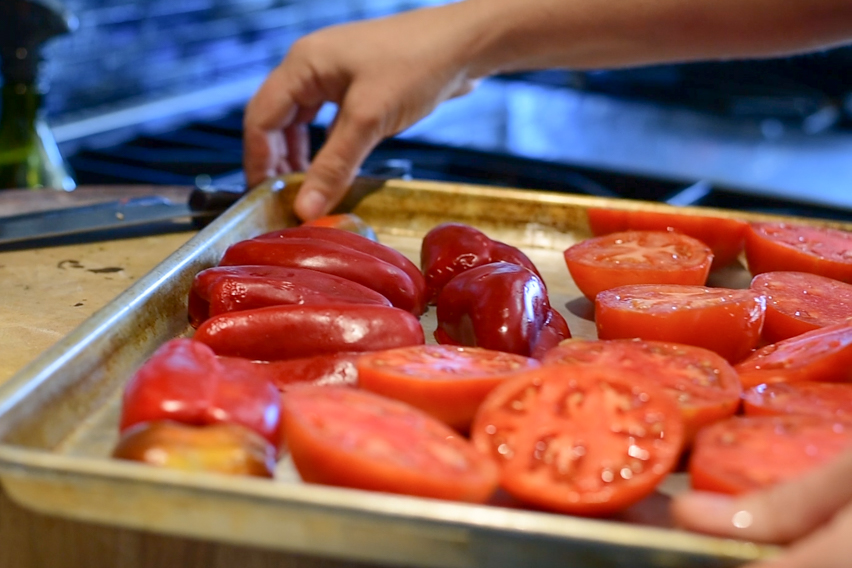 Preparing tomatoes and red peppers for broiling.