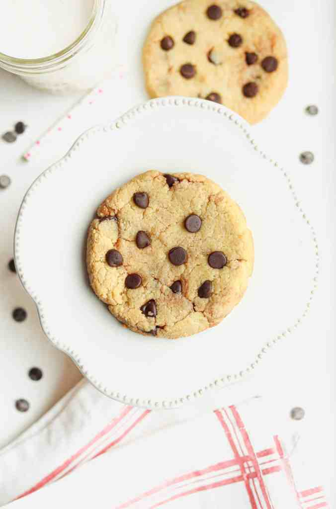 A chocolate chip cookie sitting on a raised plate.