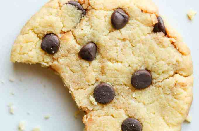 A chocolate chip cookie with a bite taken from it laying on a plate.