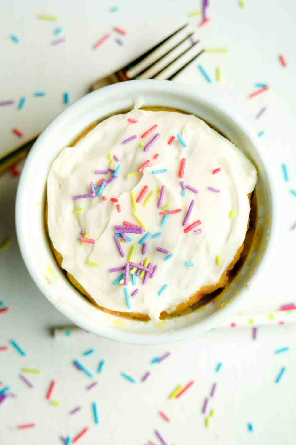 A birthday cake mug cake topped with frosting and sprinkles.