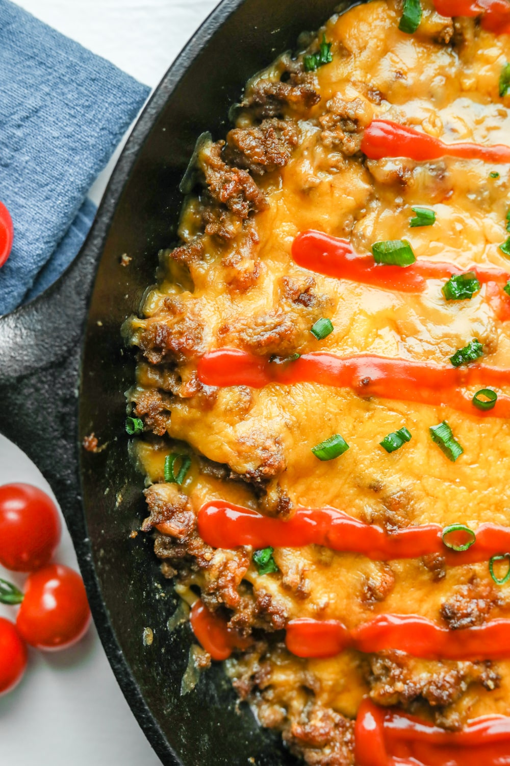 Half of a keto cheeseburger casserole covered in chives and low carb ketchup.