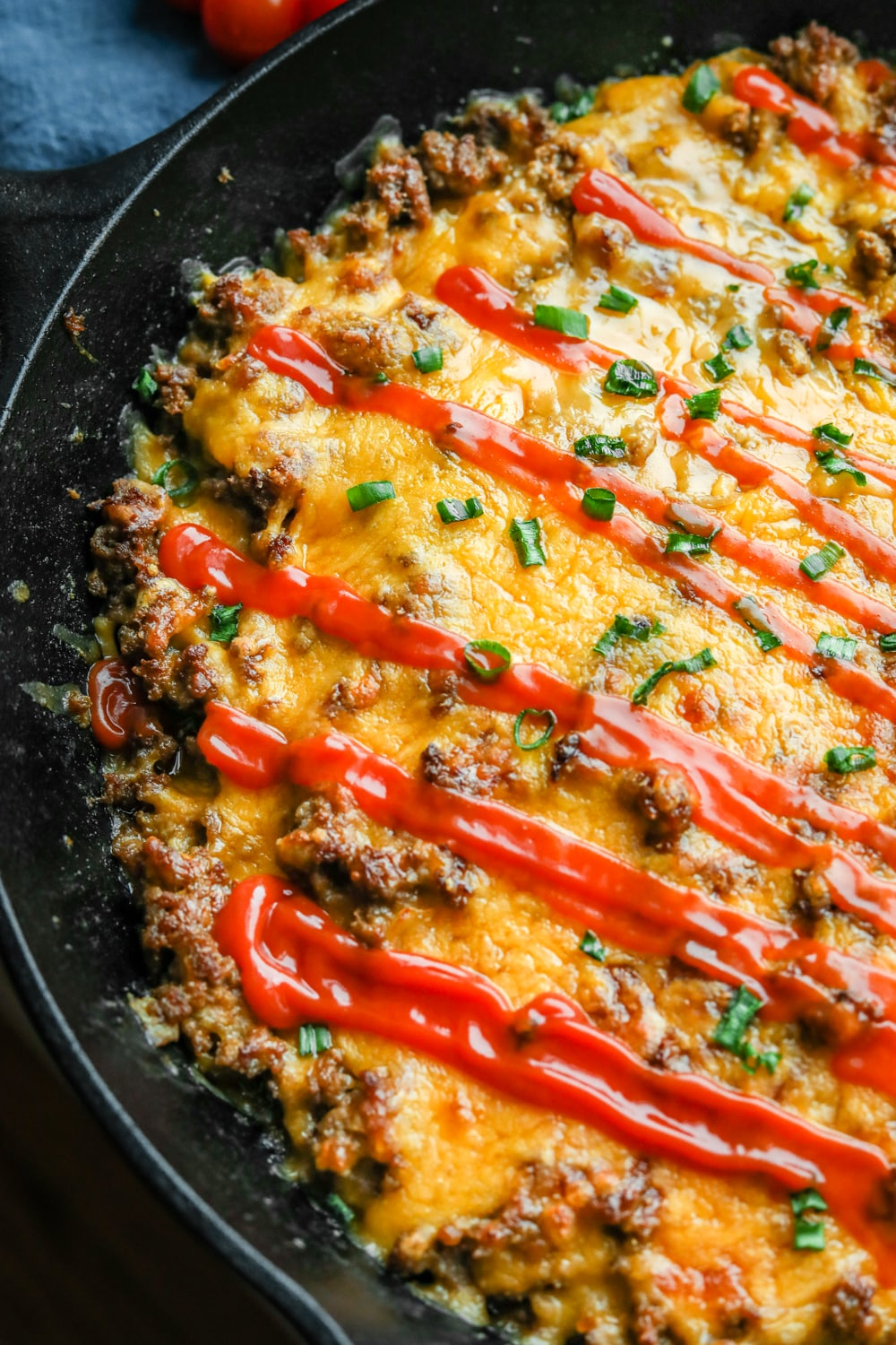 Half of a cheeseburger casserole in a cast iron pan topped with chives and keto ketchup.