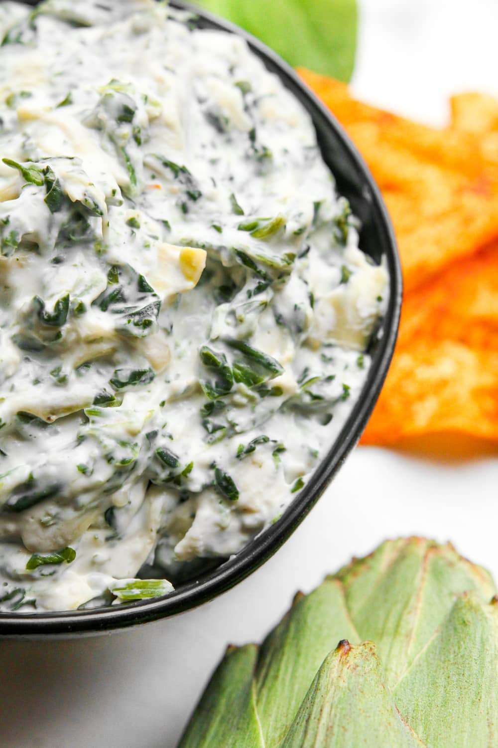 An up close view of low carb spinach and artichoke dip in a bowl.