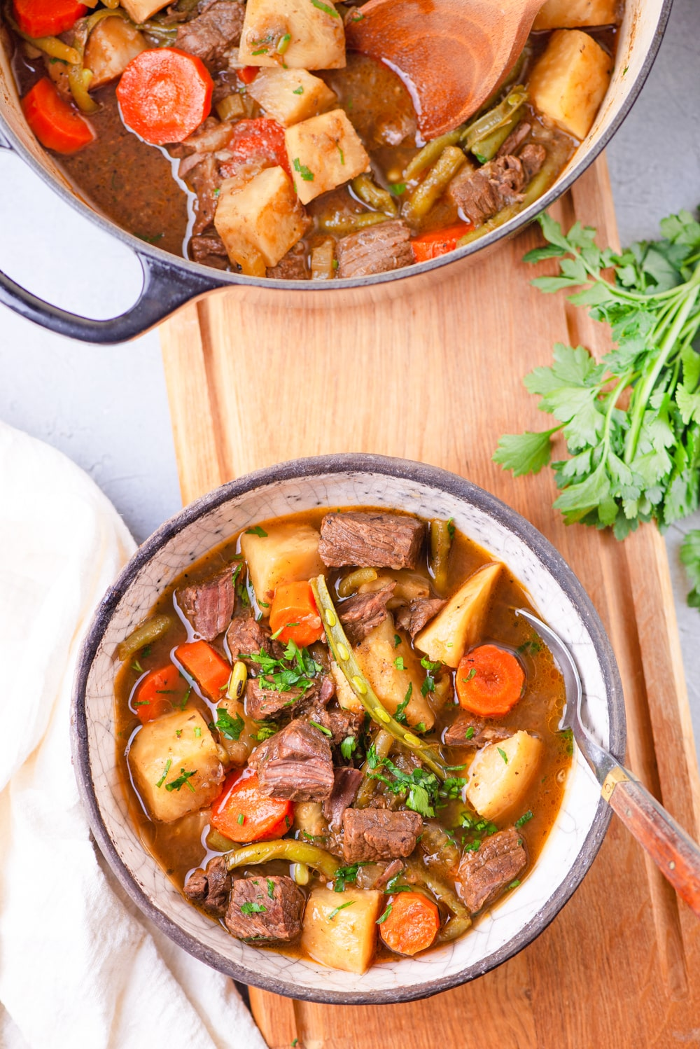 A bowl of keto beef stew next to fresh herbs.