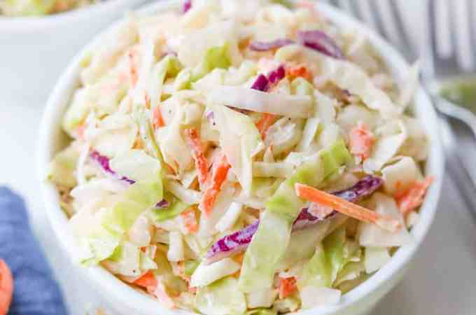 Keto coleslaw in a small white bowl, surrounded by carrots, cabbage, and a blue napkin.
