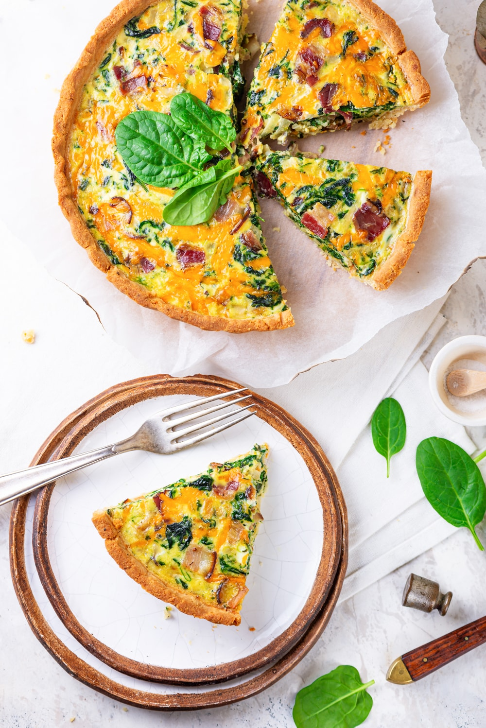 A slice of keto quiche on a plate, while the rest of the quiche is set and cut next to it.