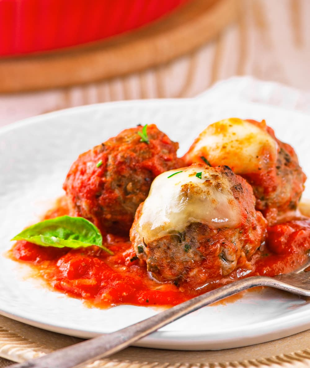 3 Meatballs on a plate covered in tomato sauce.